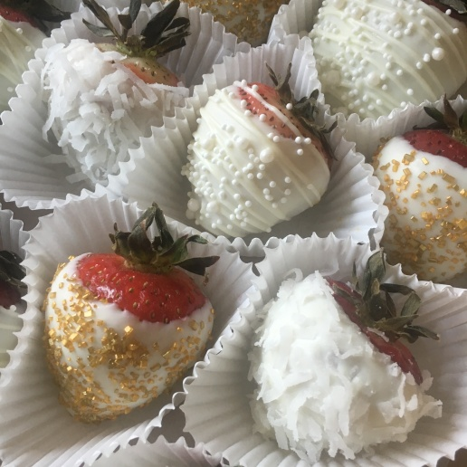 Gourmet white and gold, chocolate covered strawberries with shredded coconut and sprinkles
